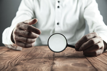 Businessman showing magnifying glass. Business concept
