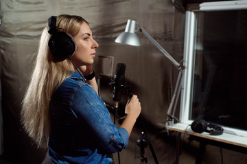 Female singing a sing with mobile phone at recording studio. You
