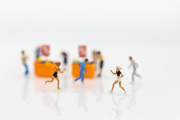 Miniature people : Shoppers running to shopping, discount product sale . Image use for retail business concept.