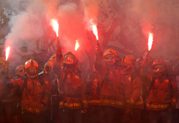Firemen raise up flares during a protest against cuts and working conditions in front of Catalonia Parliament in Barcelona