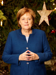German Chancellor Angela Merkel poses for a picture in front of a Christmas tree at the federal Chancellery in Berlin