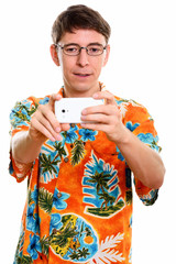 Studio shot of man taking picture with mobile phone