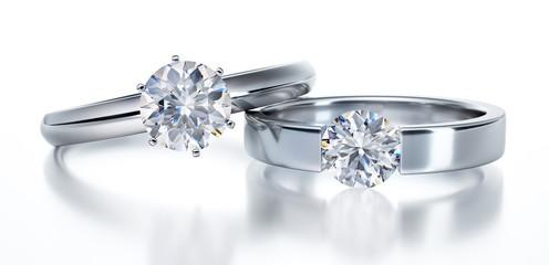 2 Solitär-Diamantringe liegend auf Weiß