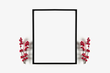 Christmas modern composition. Photo frame, red berries on white background. Christmas, New Year, winter concept. Flat lay, top view, copy space