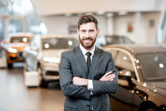 Portrait of a handsome salesman in the suit standing at the showroom with luxury cars on the background