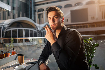 Picture of young man sitting at table and smoking. He look up to right. Guy lean on table. He sit outside. Sun is shining.