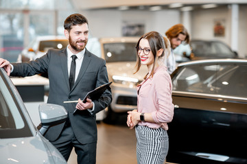 Car salesman helping to a young woman client to make decision showing a new car at the showroom