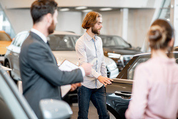 Young couple with salesperson choosing a new car looking on the back seats in the showroom