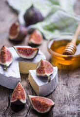 Homemade soft cheese, figs, grape on a wooden background with copy space.