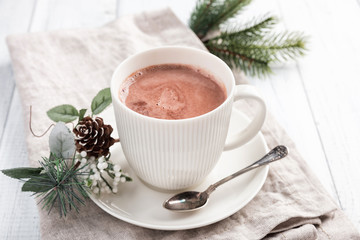 Cup of hot chocolate on the white wooden table. Winter cocoa drink on a napkin