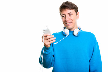 Happy man smiling while wearing headphones around neck and using