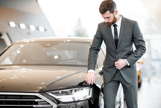Portrait of an elegant businessman touching headlight of a luxury car in the showroom