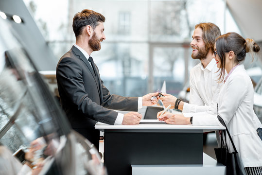 Young business couple signing some documents at the table with salesperson or manager buying or renting car in the showroom