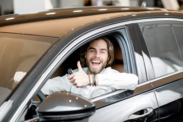 Portrait of a happy owner sitting on a driver seat of a new luxury car at the showroom