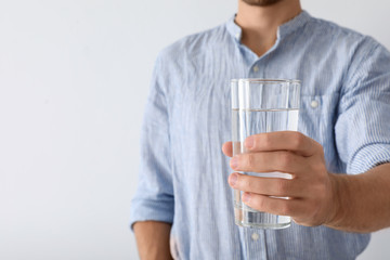 Man holding glass of pure water on white background, closeup