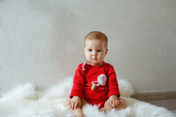 A little girl at the photo shoot, dressed in red coat.