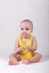 Cute baby boy wearing yellow bodysuit sitting on carpet and holding glasses
