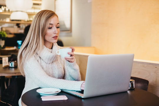 Lady using laptop at table with cup of drink and smartphone