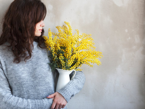 girl with a bouquet of mimosa near an empty wall