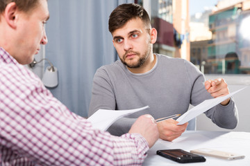 Troubled man discussing documents with male at home table