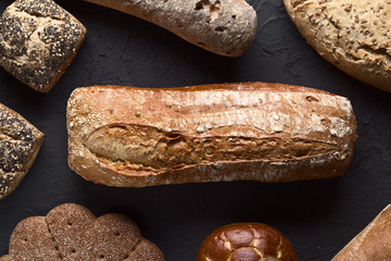 top view of group of rustic breads on dark background
