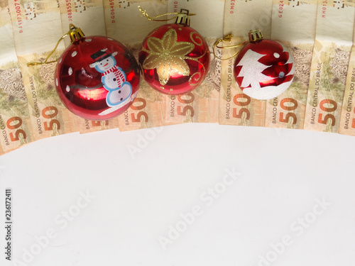 Christmas decorations with Christmas balls on brazilian money. Saving money concept. Working in holiday. Black friday concept. White background with copy ...
