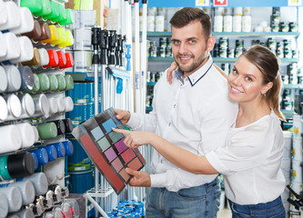 man and  woman choosing color for painting