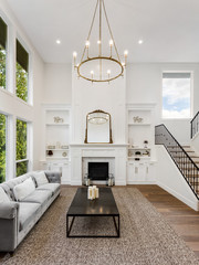 Beautiful Living Room in New Luxury Home with Fireplace. Large Bank of Windows Shows Exterior View of Trees. Vertical Orientation