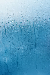 Window glass with high humidity condensation. Natural water background. Vertical photo. Copy space