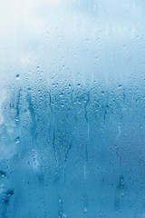Window glass with high air humidity, large drops drip. Background of natural water condensation