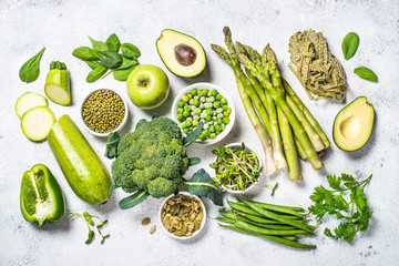 Green food assortment on light stone background.
