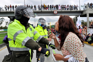 A student blows soap bubbles at a policeman during a march to demand more resources from the government to finance public education, in Bogot