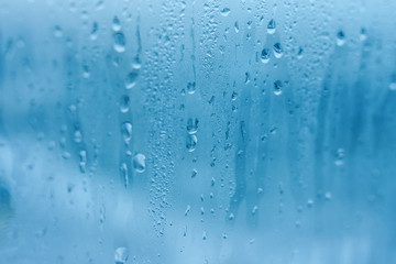 The texture of natural water drops on glass. High humidity indoor. Close-up with condensation