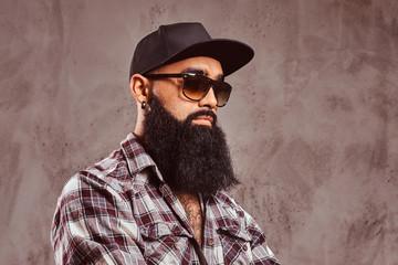 A bearded arabian male wearing checkered shirt sunglasses and cap.