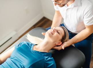 A Modern rehabilitation physiotherapy man at work with woman client working on neck