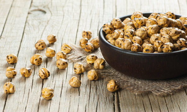 turkish leblebi, famous nut, stack of yellow roasted chickpea in brown bowl on wooden rustic background, roasted chickpeas