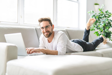 A Young attractive guy is browsing at his laptop, sitting at home on the cozy beige sofa at home, wearing casual outfit