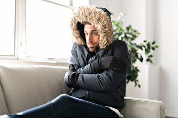 A Man have cold on the sofa at home with winter coat