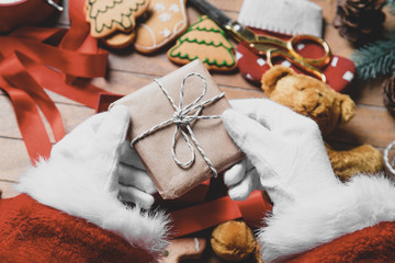 Santa Claus have wrapping a Christmas present box and other gifts on wooden background
