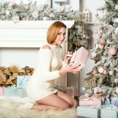 an elegant woman in a knitted dress sits on her lap on a fur rug and holds her box with gift to New Year in her hands near Christmas tree in the room