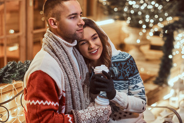 A young romantic couple wearing warm clothes outdoor at Christmas time, sitting on a bench and warming with hot coffee in evening street decorated with beautiful lights.