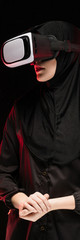 Portrait of beautiful smart young muslim woman wearing black hijab using virtual reality headset on black background