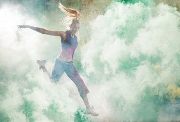 Portrait of a jumping dancer holding colorful flares