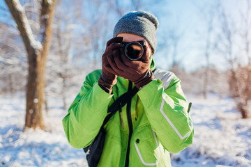 Young photographer takes pictures of winter forest using camera. Young man shooting photos outdoors