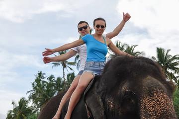 Portrait of a happy young couple on an elephant. Tropical coast of Sri Lanka