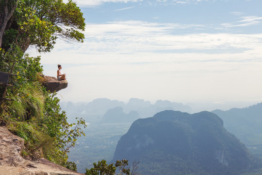 Young woman sitting on top of a mountain and relaxing
