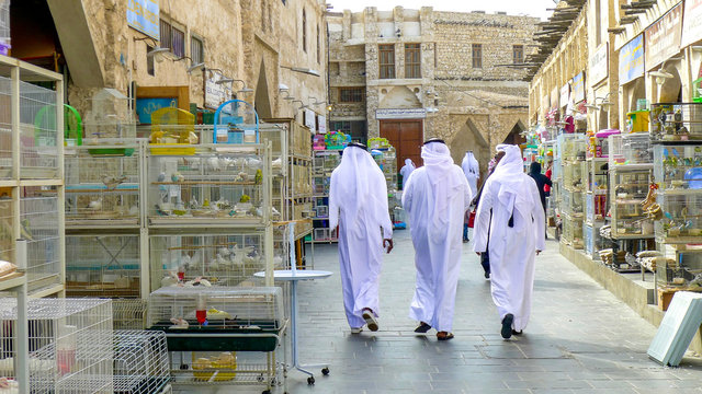 Three men in traditional Qatari dress walk between bird cages and animals for sale in Souq Waqif market in Doha's old town, Qatar