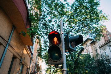 Urban, street traffic lights. The red sign for pedestrians is lit.
