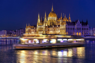 Fototapete - Parliament building of Budapest above Danube river in Hungary at night.