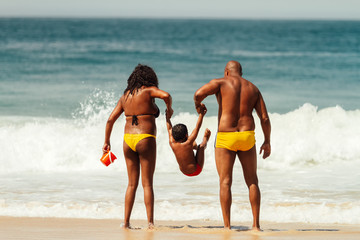 African American parents jump their son on the seashore during the morning at Copacabana beach